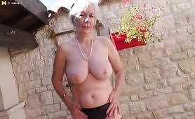 Hoary British granny getting wet in her garden